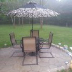 Metal table with four chairs umbrella on patio