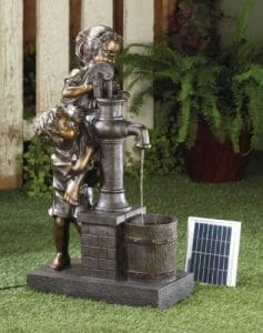 Boy and Girl pumping water in a solar fountain