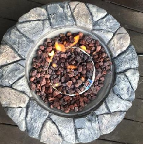 Backyard Stone Fire Pit-Peaktop fire pit top view with lava rocks and fire